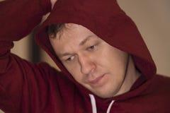 Stående av en ung man i en huv, fundersam blick, närbild arkivfoto
