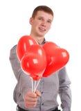 Stående av en ung man med ballonger Arkivbild