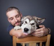 Stående av en ung man med en hund arkivbilder