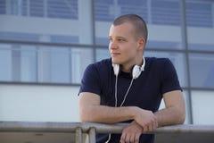 Stående av en ung man med hörlurar som framme står av Arkivbild