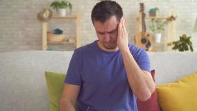 Stående av en ung man med en huvudvärk stock video