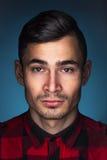 Stående av en ung man på blå bakgrund Fotografering för Bildbyråer