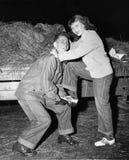 Stående av en ung man som hjälper en ung kvinna att stiga ombord en släp (alla visade personer inte är längre uppehälle, och inge Royaltyfri Foto