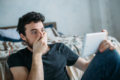Stående av en ung man som kopplar av och håller ögonen på en TV-program på en minnestavladator royaltyfria foton