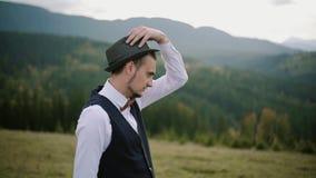 Stående av en ung man som av naturen omges Man som slitage en hatt långsam rörelse arkivfilmer