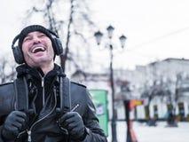 Stående av en ung man som skrattar och lyssnar till musik på en gata Arkivbild
