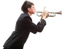 Stående av en ung man som spelar hans trumpet Fotografering för Bildbyråer