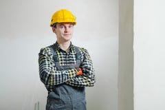 Stående av en ung manlig byggmästare och repairman i en gul hjälm mot bakgrunden av en vägg royaltyfri foto