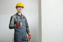 Stående av en ung manlig byggmästare och repairman i en gul hjälm mot bakgrunden av en vägg royaltyfria foton