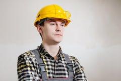 Stående av en ung manlig byggmästare och repairman i en gul hjälm mot bakgrunden av en vägg arkivfoto