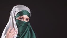 Stående av en ung modern muslimsk kvinna i en hijab på svart bakgrund stock video