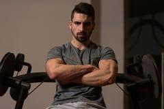 Stående av en ung muskulös idrotts- man som poserar, medan sitta A Royaltyfri Bild