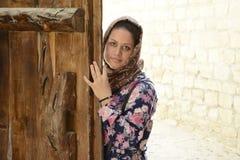 Stående av en ung muslim kvinna bak trädörr arkivbild