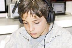 Stående av en ung pojke som lyssnar till musik på hörlurar Royaltyfri Foto