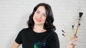 Stående av en ung positiv kvinnlig målare som rymmer variation av borstar som trycker på några av dem Målare för ung kvinna i a lager videofilmer