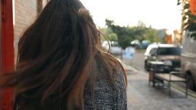 Stående av en ung sexig kvinna som går runt om staden, hår som fladdrar i vinden Ultrarapidskott stock video