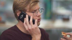 Stående av en ung skäggig grabb med exponeringsglas som äter en smörgås och talar på mobiltelefonen lager videofilmer