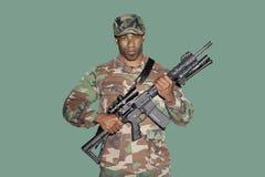 Stående av en ung soldat för afrikansk amerikanUSA Marine Corps med geväret för anfall M4 över grön bakgrund Royaltyfri Foto