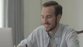 Stående av en ung stilig man som ler och nickar att sitta framme av hans dator i kontoret Kontorsarbetaren lager videofilmer