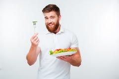 Stående av en ung stilig tillfällig man som äter sallad arkivbilder