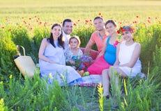 Stående av en ung stor gravid familj i vallmofält Arkivbilder