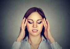 Stående av en ung stressad kvinna med huvudvärk royaltyfri fotografi