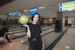 Stående av en ung student med en boll för att bowla i hennes händer Flickan spelar bowling och poserar på kameran Arkivfoto
