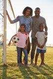 Stående av en ung svart familj bredvid ett fotbollmål royaltyfri foto