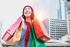 Stående av en upphetsad härlig hatt för för ung flickakläderskjorta som och ull rymmer många shoppingpåsar och leende Med kopiera royaltyfri foto