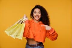Stående av en upphetsad ung afrikansk kvinna som rymmer shoppingpåsar och visar kreditkorten som isoleras över beige bakgrund arkivfoton