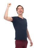 Stående av en upphetsad ung man med armen som lyfts upp Arkivfoto