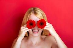 Stående av en uppnosig kvinna med blomman Royaltyfri Fotografi