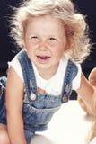 Stående av en uppriven liten flicka i grov bomullstvilloveraller som sitter i en studio på svart bakgrund royaltyfri bild