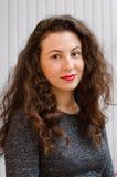 Stående av en ursnygg brunettkvinna med krabbt hår och härligt leende Fotografering för Bildbyråer