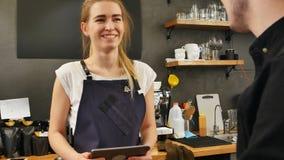 Stående av en ursnygg kvinnlig barista som tar beställningen av en kund med en dator och le för minnestavla Royaltyfri Fotografi