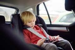 Stående av en uttråkad pys som sitter i ett bilsäte Säkerhet av barn arkivfoto