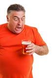 Stående av en uttrycksfull fet man som dricker öl royaltyfria bilder