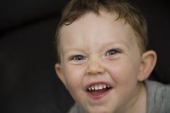 Stående av en uttrycksfull härlig blond pojke mot en svart bakgrund Arkivfoto