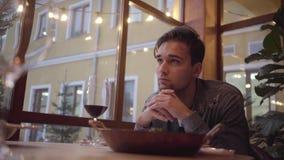 Stående av en väntande på matställe för stilig skäggig ledsen grabb i ett kafé eller en restaurang stock video