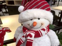 Stående av en vit leksaksnögubbe med en röd halsduk och en röd ljus hatt arkivbilder