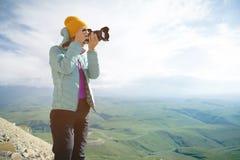 Stående av en yrkesmässig fotograf i den öppna luften En flickafotograf tar bilder av hennes kamera på hennes kamera arkivbild