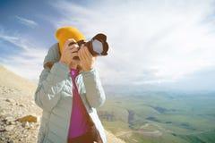 Stående av en yrkesmässig fotograf i den öppna luften En flickafotograf tar bilder av hennes kamera på hennes kamera arkivfoton