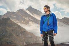 Stående av en yrkesmässig handbok av en bergsbestigare i ett lock och solglasögon med en isyxa i hans hand mot fotografering för bildbyråer