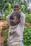 Stående av ett angolanskt barn, med den mycket uttrycksfulla framsidan, med hennes broder på bakgrund arkivfoton