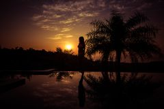 Stående av ett anseende för ung kvinna mot en ursnygg solnedgång arkivbild