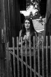 Stående av ett anseende för ung kvinna nära ett trästaket i byn Royaltyfri Bild