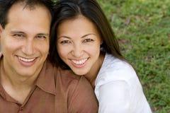 Stående av ett asiatiskt par som skrattar och kramar Arkivbild