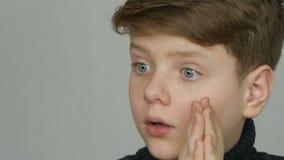 Stående av ett blont och blåögt roligt för tonåringpojke som framme förvånas av kameran på vit bakgrund Sinnesrörelser av lager videofilmer