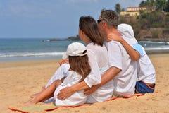 Stående av ett familjsammanträde på den sandiga stranden royaltyfri bild