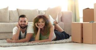 Stående av ett gift par som ligger på golvet, når att ha flyttat sig arkivfoto
